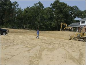 A bulldozer grades a portion of the parking lot area at the Bowling Green library branch.