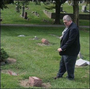 Police Lt. David Schmidt locates a headstone in Forest Cemetery engraved with the name Conrad Yahn.