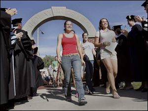 Freshmen stride through Griffith Memorial Arch as faculty members cheer them on.