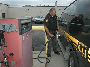 Deputy David Lindhorst refuels at the Lucas County garage. Many area governments are trying to address rising gas prices.