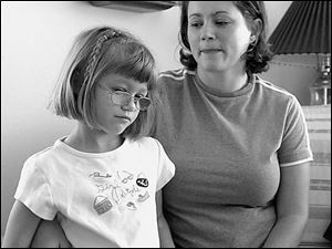Alyssa Stec, 6, tells her mom, Stacey, what she misses about Slidell, La., while staying at her grandparents  South Toledo home.