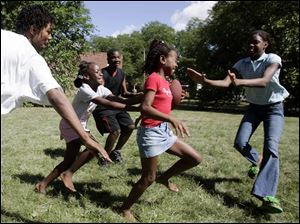Shawn Alexis, 15, Jasmine Dandridge, 9, Kevin Dandridge, Jr., 15, Kyira Alexis, 11, and Walkeya Alexis, 12, from left, play football in central Toledo. Except for Kevin, all are displaced hurricane victims who fled New Orleans in a three-vehicle caravan before Katrina hit.