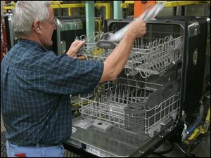 Jack Glick places an instruction manual into a finished dishwasher during final assembly at Whirlpool's Findlay operation.
