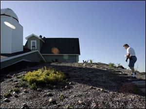 Ralph Semrock, whose goal is energy self-reliance, mounts the earth-bermed rear of his home.