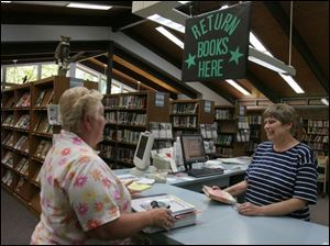 Jane Kohlenberg, right, director of the Pemberville Public Library, discusses library services with Diane Henry.