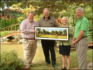 Mark Reilly, left, and Nancy Reilly with a painting by John