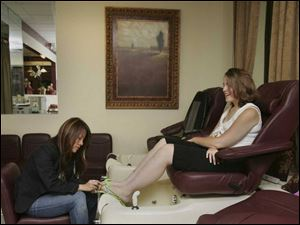 Jacquelyn Duslak gets a pedicure from Mindy Nguyen, who says customers enjoy a little pampering.