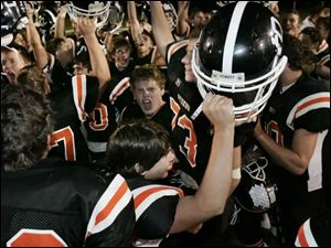 Otsego players, including backup quarterback Andy Cocke, bottom center, celebrate the Knights' five-overtime victory.