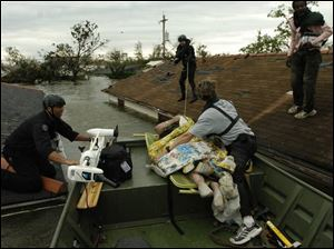 New Orleans police officers maneuver a rescue boat between the roofs of flooded houses in the city's hard-hit Ninth Ward as Times Picayune reporter Alex Brandon, right of boat, holds onto a hurricane victim.