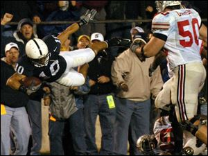 Penn State safety Calvin Lowry flies out of bounds after being tackled by Ohio State quarterback Troy Smith (on ground). Lowry had intercepted one of Smith's passes.