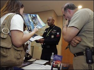 Sarah Melin, 16, left, and her father, Steve Melin, get information from Naval Reserves PO 2nd Class Kevin E. Crumble at Bowsher High School. Parents and Toledo Public Schools students not interested in the service can opt out of giving the military access to their personal data, but because of the No Child Left Behind Act, there are consequences. So far, 221 students have opted out, the district said.