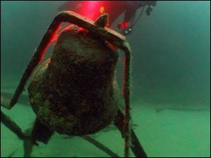 A diver takes a close look at the bell of the Sadie Thompson, a barge which sank in 116 feet of Lake Superior water near Whitefish Point in a storm in the early 1950's.