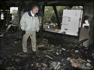 Lou Ratajski, owner of Jim and Lou's Bar, examines the damage from a fire ignited during the rioting on Saturday.