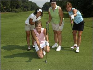 FRIENDLY TIPS: From left, Michelle Ryan, Katy Walker, and Megan Gallup give Kim Turner some putting advice on the course at Sylvania Country Club.