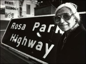 Rosa Parks stands next to a sign at Scott High School in Toledo