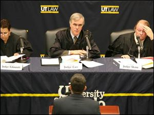 U.S. District Judges Nancy Edmunds, left, of Detroit and James Carr of Toledo and Ohio appellate Judge William Skow of Toledo listen to UT law student George Thomas.