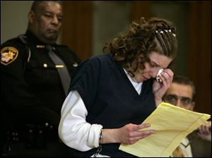 Elissa Schuster weeps as she reads a statement that reiterated her claim that she did not rape the girl, who is now 5.