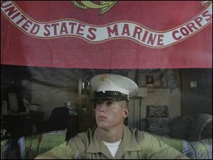 Lance Cpl. Ian Mikolajczak proudly displays a Marine Corps flag in the front window of his family's home on Schneider Road. 