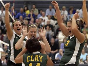 Clay High School players celebrate as they rallied against Elyria in the first game of last night's regional semifinal.