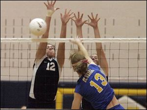 St. Ursula s Ashley Heyman (13) tries to spike the ball past two