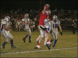 Patrick Henry's Marc Krauss hauls in a fourth-quarter touchdown for the Patriots on a seven-yard pass from Zack George despite the tackle of Elmwood defender Brian Bevelhymer.