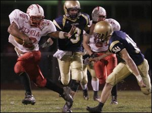 Elyria's Jaa'Rome Williams has a stiff arm ready to fend off St. John's defender Jake Bombrys last night.
