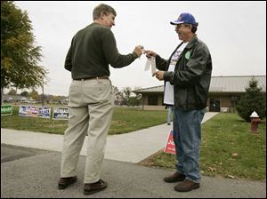 John Pristash, left, takes a sticker from Gary Munch outside the Sylvania Senior Center on Sylvania Avenue yesterday.