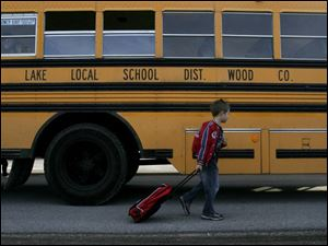 A Lake Elementary student boards a bus a day after voters in the Lake Local School District rejected a levy proposal. Past defeats have led to busing being cut to state minimums.