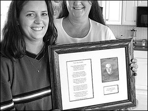 Angela Hall, left, holds a framed tribute to her late brother Billy, who died seven years ago in a traffic accident, as her mother, Leslie Hertzfeld, looks on in the family home. the blade/lisa dutton The firm's magnets can be personalized by the buyer.