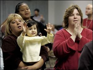 From left, Cheryl Sherman, Peggy Hydlebeerd, 2-year-old Alexia Handy, and Linda Jones clap along with the music.