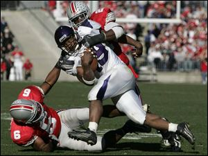 Northwestern running back Tyrell Sutton is dragged down by Ohio State senior cornerback Tyler Everett (6) and senior safety Nate Salley. Yesterday's home game was the last home game for 16 Buckeye seniors. Sutton, a freshman from Akron who was Ohio's Mr. Football last year, had 93 yards on 14 carries.