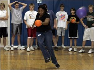 Scott High School senior Tianna Dandridge plays kickball with students from Clyde High School in a gym class during a cultural exchange program at the Sandusky County school.