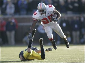 OSU running back Antonio Pittman leaps over Michigan's Morgan Trent for a first down in the fourth quarter.