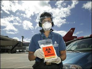 Belinda Lee holds a specimen bag that Hawaii uses to check ill airline passengers for bird flu. Hawaii is the first state to test.