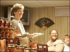 Wendy McGrady, left, hosts a Tastefully Simple party at her home in Sylvania.