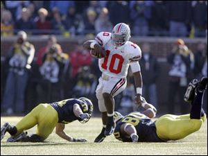 Ohio State's Troy Smith slips between Michigan's Morgan Trent, left, and Alan Branch for first down. The junior quarterback, who completed 27 of 37 passes for 300 yards, led the Buckeyes to their second straight win over the Wolverines and their fourth win in five years against UM.