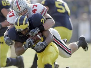 Ohio State linebacker A.J. Hawk smothers Michigan running back Mike Hart for a loss in the first quarter at Michigan Stadium. Hawk had seven tackles, giving him 382 for his four-year career. Hart was held to 15 yards rushing on nine carri
