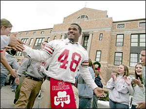 Slug: CTY central02p             Date:   12.02.05        The Blade/Madalyn Ruggiero      Location:  Central Catholic, Toledo, o  Caption:     Central Catholic football player AaronPeterson a junior   at   is mobbed by students while heading to the bus at Central Catholic Friday morning 12.2.05 just before heading to Division  11 finals tonight.