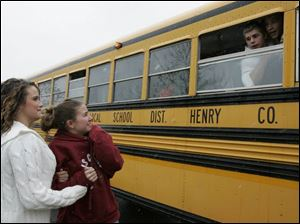 Brittany Merritt, left, and Meagan Buenger wish Patrick Henry football players good luck as the team departs for the Division V football title game today in Canton. It is the first championship game in school history.