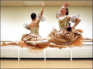 Lucy Messervy, front, and Ariel Warrick glide gracefully through the air in a scene from <i>The Nutcracker</i>.