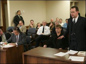 Neo-Nazi spokesman Bill White, standing, argued against an injunction sought by the city of Toledo barri