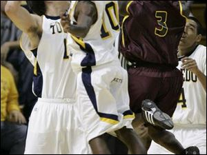Toledo's Allan Pinson, left, blocks a shot by Ferris State's Dennis Springs, right. Kashif Payne (10) is also in the play.