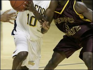 Kashif Payne of the Rockets drives against Dennis Springs of Ferris State in first-half action at Toledo's Savage Hall.