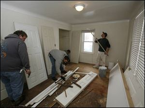 From left, Chuck Bennett, Bob Gerber, and Ed Matuszynski tackle a bedroom of a 'distressed' house owned by Juscot Realty.