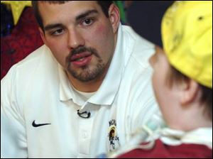 Michigan offensive lineman David Schoonover, left, talks to Kenny Winder. Schoonover has visited Mott Children's Hospital weekly for five years.