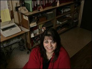 Rogers High School secretary Norma Hernandez does double duty as the school's cheerleading coach.