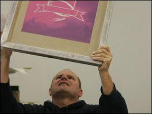 Ken Kaczorowski, silk-screen manager at Team Sports Inc., checks for pinholes in a just-completed screen.