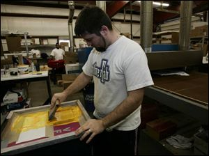 Jon Iwinski silk-screens the yellow onto University of Toledo GMAC Bowl T-shirts at Team Sports Inc.