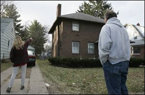 The mother of 'Stacy' points to the house where her daughter and niece 'Cara' were held, while Cara's father looks on.
