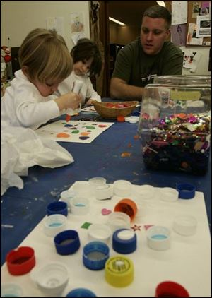 Perrysburg residents Grace Burkin, 2, left, and her sister Hope, 5, create bottle-cap art at the Toledo Museum of Art's Family Center while their father, Donny, offers helpful tips.